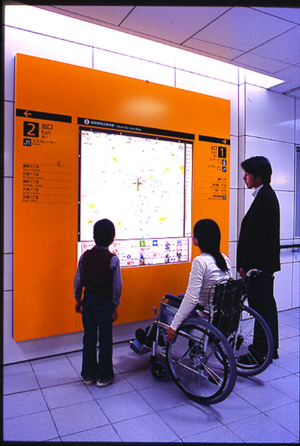 This shows a family watching the information screen at the station