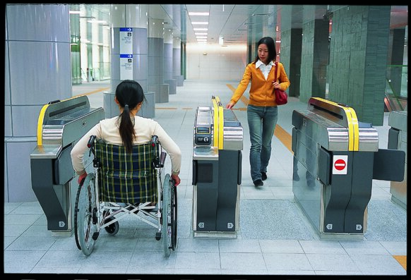 woman in wheelchair entering the station through the gate
