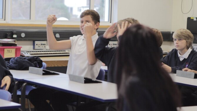 This photo shows boy cheering in a classroom.